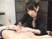 Sassy Asian masseuse giving an erotic handjob to a huge dick