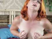 Red mature slut playing with her hairy pussy